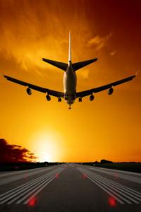 jumbo jet airplane landing on runway at sunset, vertical frame